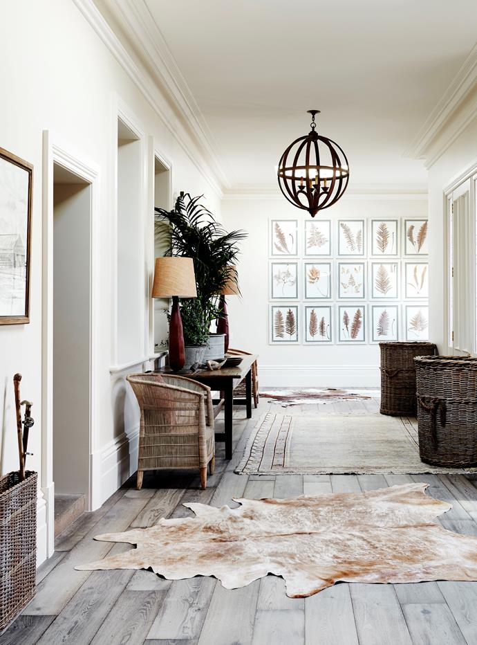 African lampbases, antique rug, cowhides and wool baskets in the entry.