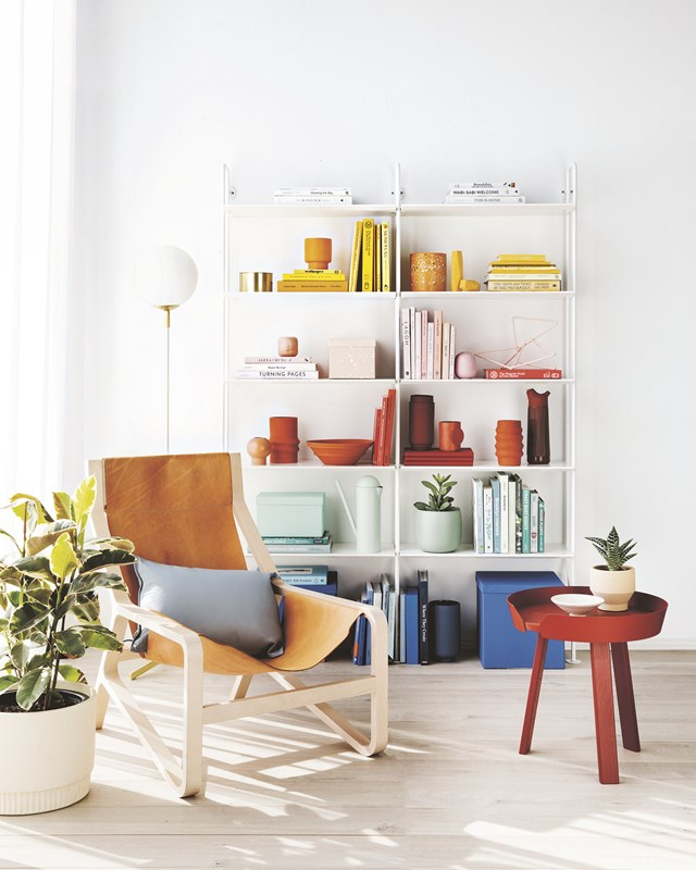 Arranging your books and home decor by colour might be a no-no for people who prefer an anywhere-it-fits route, but it does make shelves look less cluttered and creates a focal point. *Photo:* Sam McAdam-Cooper
