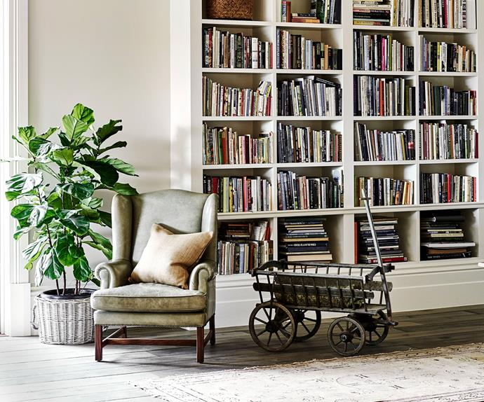 A leather wing back chair in front of a book shelf