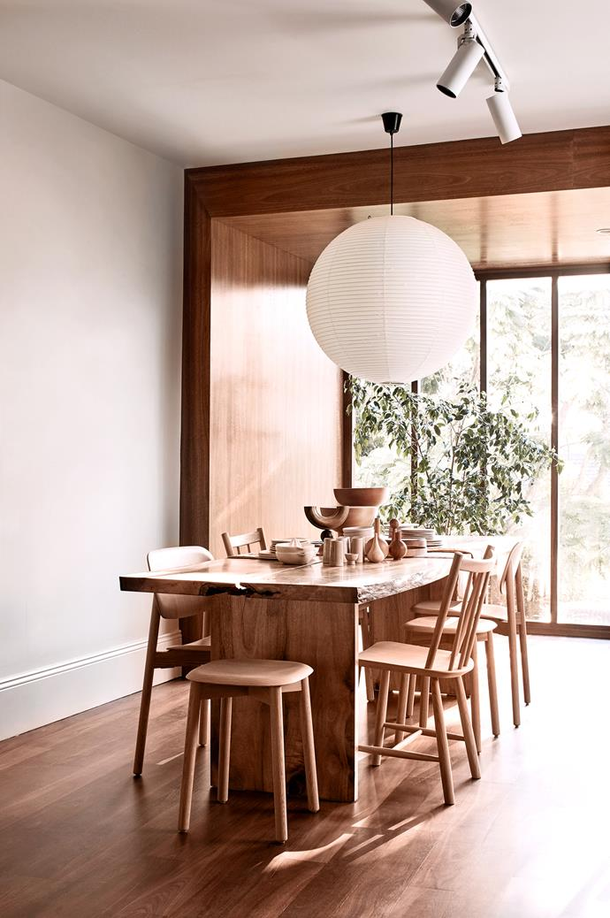 """The back of the store is referred to as the """"log cabin"""", as it's clad in timber and looks out to the leafy surrounds. An Akari """"Noguchi 55A"""" pendant lamp hangs above a custom-designed table by We Are Triibe."""