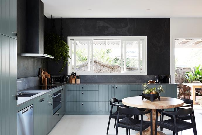 Sage greens, deep navy and concrete grey tones create a contemporary feel in the kitchen.