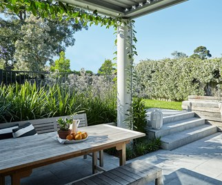 Outdoor dining area beneath a pergola overlooking backyard