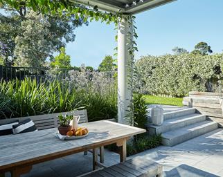 Outdoor dining area beneath a pergola overlooking backyard