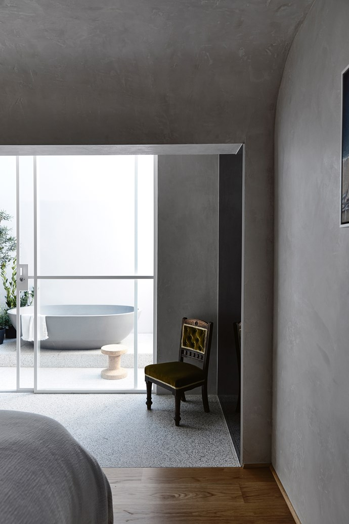 "The cavernous master bedroom in a [renovated Church in Hawthorn](https://www.homestolove.com.au/renovated-church-in-melbourne-6912|target=""_blank"") opens out onto a private courtyard bathroom. It's a bold design that works with the home's layout. *Photo: Derek Swalwell / Story: Country Style*"