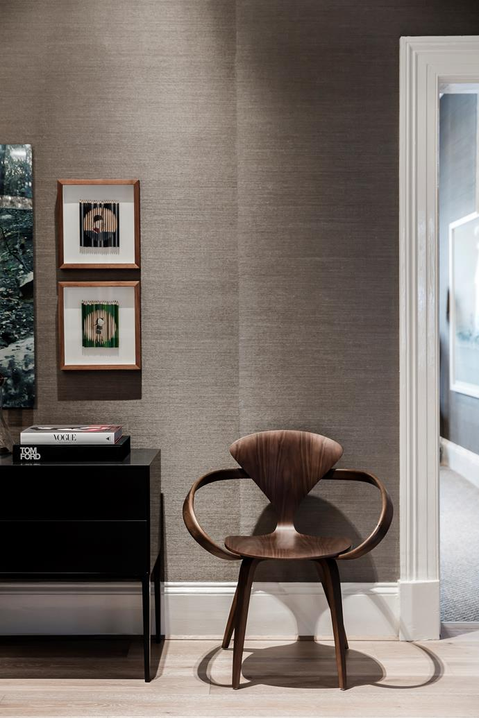 In the gallery/formal dining room, grasscloth wallpaper creates a shimmering backdrop for artworks by Janet Laurence and a vintage 'Pretzel' armchair by Norman Cherner.