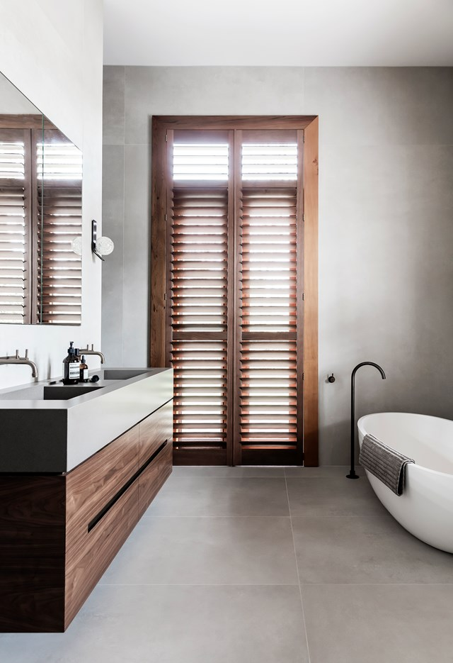 "Custom timber cabinetry gives this ensuite in a [restored 19th Century bluestone building](https://www.homestolove.com.au/colourful-restoration-of-a-19th-century-bluestone-building-6934|target=""_blank"") a pronounced day-spa vibe. Large concrete-look wall and floor tiles adding to the room's calming ambience. *Photo: Maree Homer / Story: Belle*"