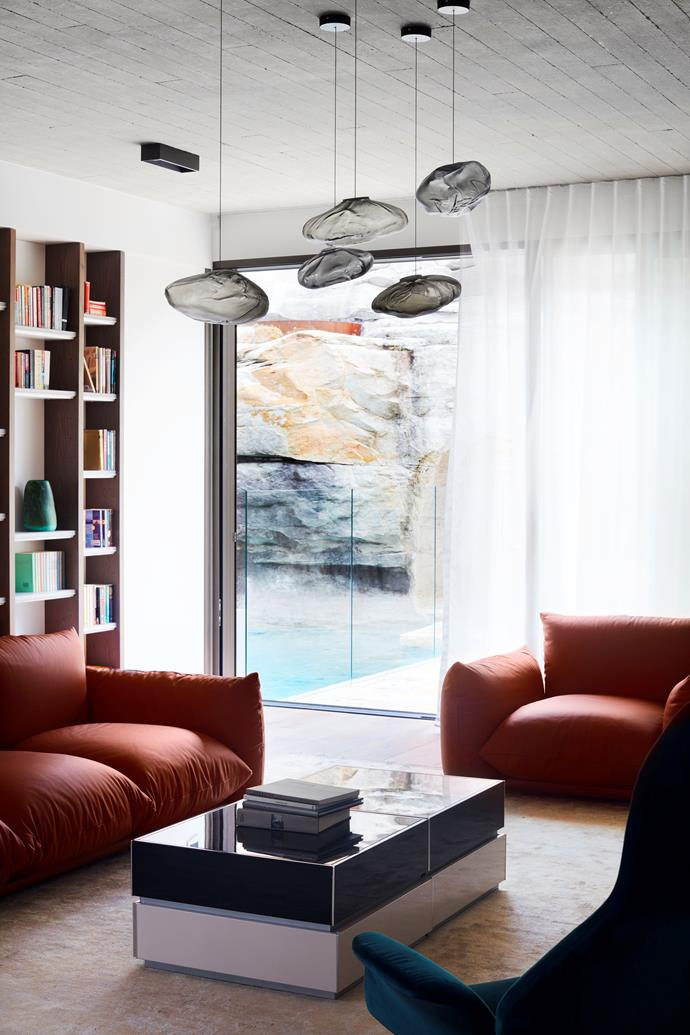 Both the study and the living area look onto the small swimming pool and rock face.