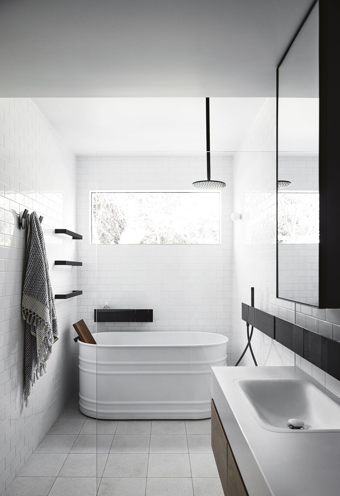 "Few colour palettes are quite as crowd-pleasing as white, black and a dash of timber. This [bathroom created by Carole Whiting](https://www.homestolove.com.au/bathroom-ideas-that-will-transform-your-zen-space-6963|target=""_blank"") shows us how it's done. *Photo: Sharyn Cairns*"