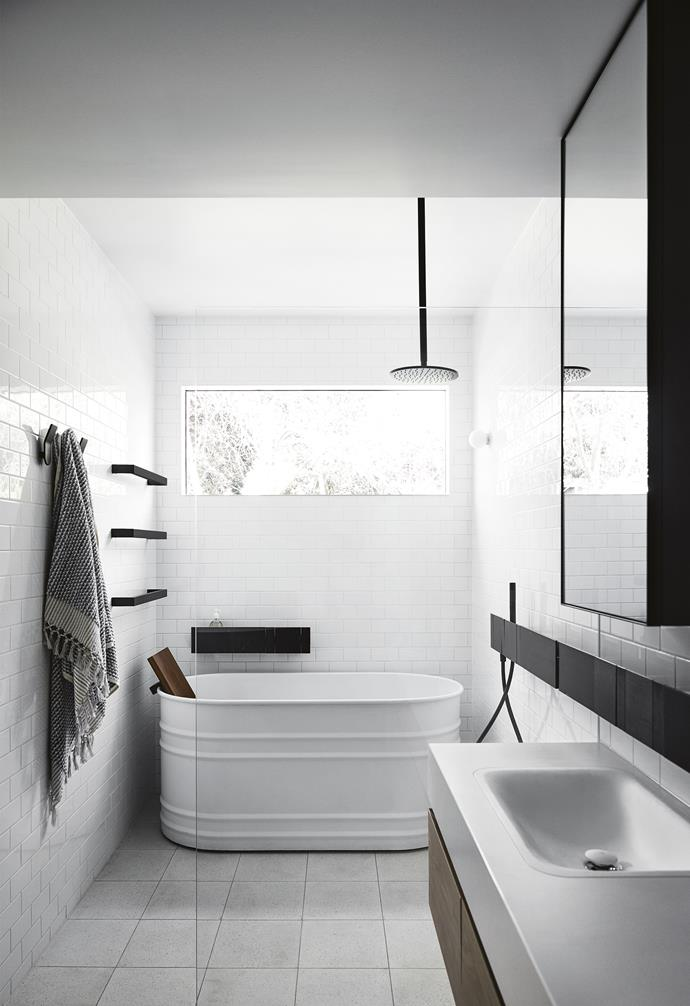"**Split personality** In order to make the most of limited space in this small bathroom, the walk-in shower and freestanding tub were sectioned off with a glass screen. A white palette maximises the light from the high window, while the black showerhead and towel rails punctuate the space. A narrow black shelf and floor-to-ceiling subway tiles unite the two sections. *Design: [Carole Whiting Interiors + Design](https://www.carolewhiting.com/|target=""_blank""