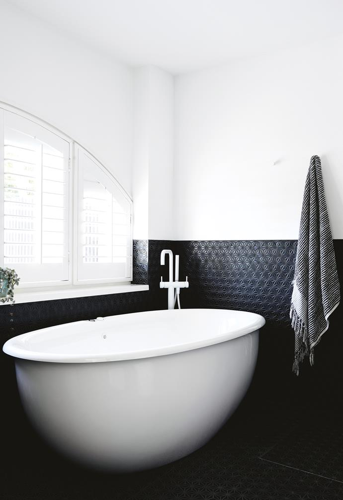 "**Balancing act** It's possible to highlight existing architectural features while creating a user-friendly bathroom, with all the luxe, modern additions you'd expect. A freestanding tub slots easily beneath an original arched window in this new ensuite addition that reclaimed space from a huge bedroom. The black Japanese tiles extend halfway up the wall to create a moody, contrasting space below, lightened by fresh white on the top half. *Design: [Northbourne Architecture + Design](http://northbourne.co/|target=""_blank""
