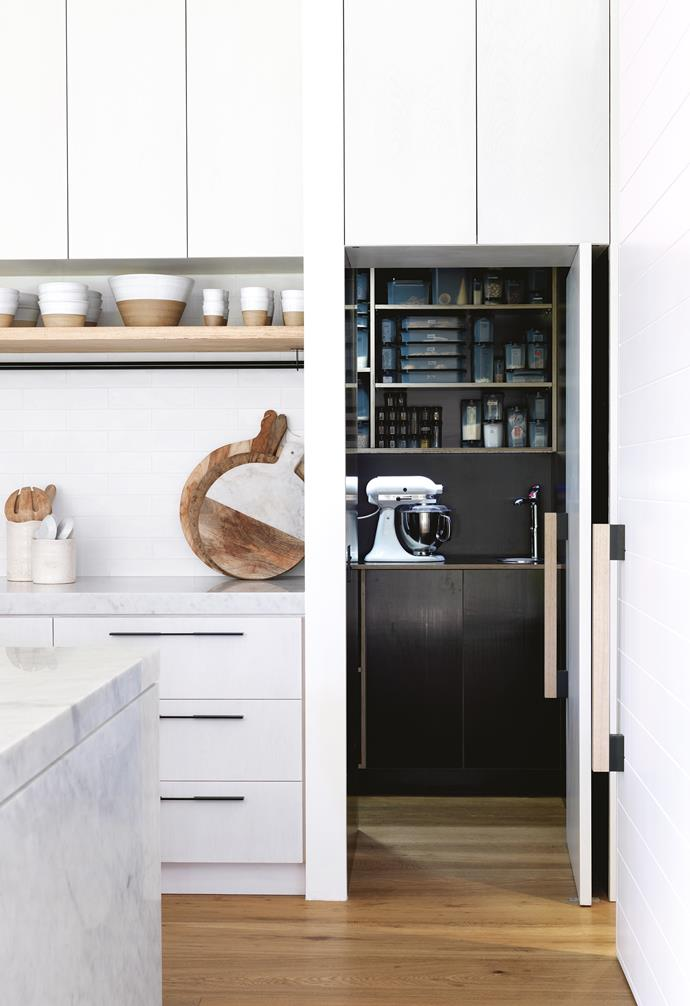 "**Back in black** Dark cabinetry allows a messy space to recede from the bright and tidy main kitchen. Built into the otherwise dead area under the stairs, this pantry can be completely hidden behind a pivot door. *Design: [Alwill Interiors](http://www.alwill.com.au/|target=""_blank""