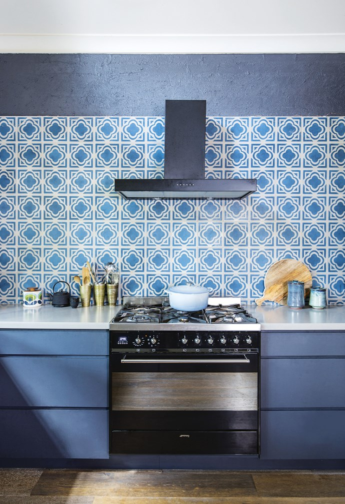 **Boho twist** The Moroccan-style encaustic tiles on this splashback add a bohemian twist to this mostly dark-toned kitchen. The dramatic pattern is complemented by the soft grey benchtops and deep blue cabinetry. *Styling: Clair Wayman | Photography: Tanika Blair*.
