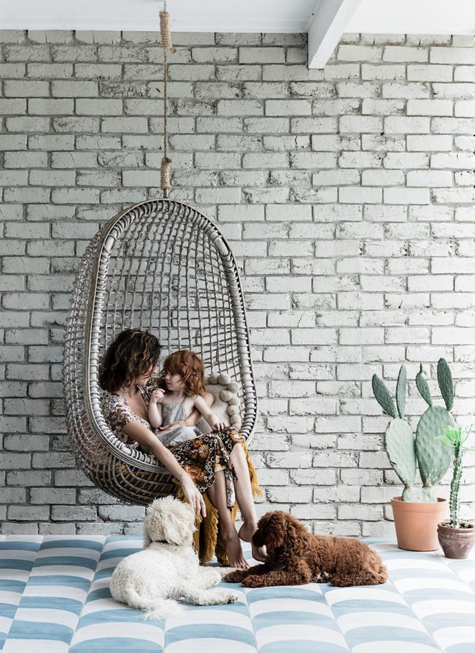 "A custom-made egg swing makes for a [relaxing outdoor sitting area](https://www.homestolove.com.au/12-outdoor-seats-that-will-have-you-relaxing-in-no-time-5925|target=""_blank"") that runs between the boys' bedroom and the kitchen. ""It's where we hang on hot days, as it usually stays cool in the shade of a big camellia tree,"" Chloe explains."