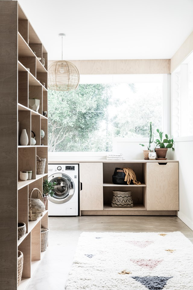 """Budget-friendly plywood storage and oodles of benchspace tick off the practical requirements, while a collection of plants, baskets and flea-market finds add personality to the laundry in this [boho Byron Bay home](https://www.homestolove.com.au/a-1970s-byron-bay-bungalow-updated-with-hygge-style-6983