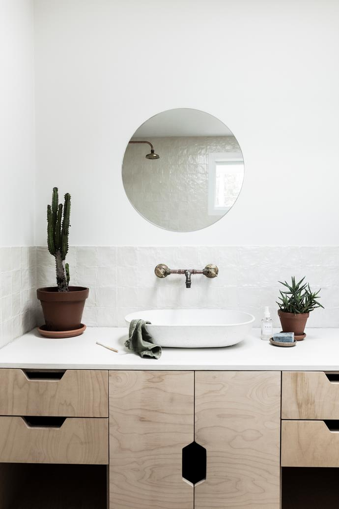 "All the home's plywood cabinets, including those in the vanity, feature the same handle cut-outs. ""Our kids are notorious for breaking handles off things, so this tackled that dilemma,"" Chloe explains."