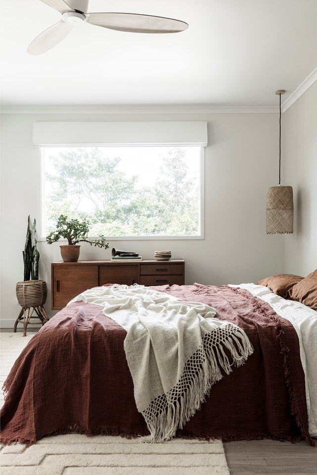 "Earthy tones and natural textures create a pared back boho vibe in this [Byron Bay home](https://www.homestolove.com.au/a-1970s-byron-bay-bungalow-updated-with-hygge-style-6983|target=""_blank""). ""Over the years I've gathered pieces from our travels, including wooden carvings, hand-drawn sketches, knitted throws and beautiful Danish sideboards,"" says homeowner Chloe. *Photo:* Maree Homer"