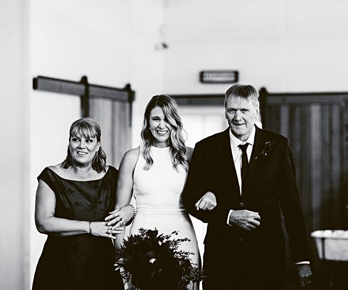 """Jenah walks down the aisle with her parents in a dress by renowned Melbourne designer [Suzanne Harward](https://suzanneharward.com/