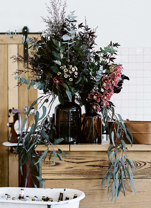 """**Natives**<br> Orchids, eucalyptus and other natives arranged in brown glass bottles, bring the bush to the city at this [warehouse wedding in West Melbourne](https://www.homestolove.com.au/stylish-relaxed-warehouse-wedding-6935 target=""""_blank"""")."""