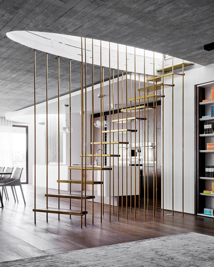 Brass pipes that support the staircase to the rooftop act as a divider between the living area and the kitchen.