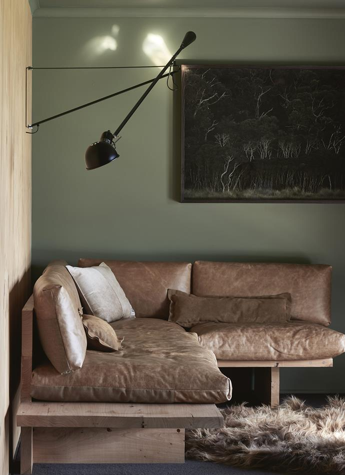 In the living room, the colour palette reflects the cabin's natural surrounds with walls painted in Dulux Colorbond Pale Eucalpyt. Andrea designed the corner sofa and her father made the base. The photograph of nearby Wilsons Promontory National Park was taken by Andrea's brother Lachlan Moore. *Photography: Lachlan Moore*