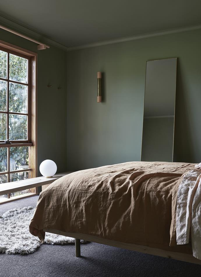 """Andrea designed the brass and wood wall light in the bedroom. Lindsay made the brass-edged mirror to tie in with the light. The bedding is from [In Bed](https://inbedstore.com/ target=""""_blank"""" rel=""""nofollow""""). *Photography: Lachlan Moore*"""