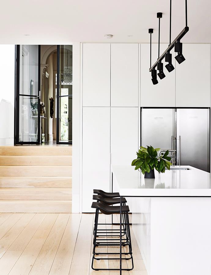 All-black fixtures give this kitchen a fuss-free visual punch. The mainly-white kitchen is anything but stark thanks to blonde hardwood flooring, the harmonious mix of textures affording the space a fresh yet timeless look. *Photography: Derek Swalwell / Bauersyndication.com.au*
