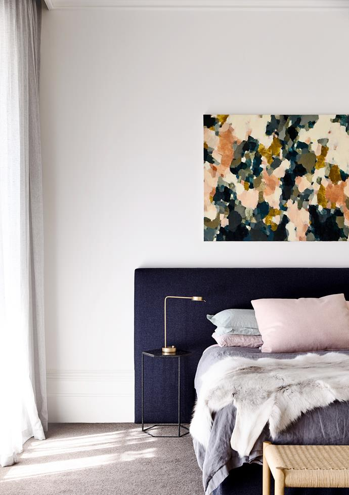 An artwork by Hannah Fox above the custom headboard in fabric from Instyle. Bedside lamp by David Chipperfield from Euroluce.