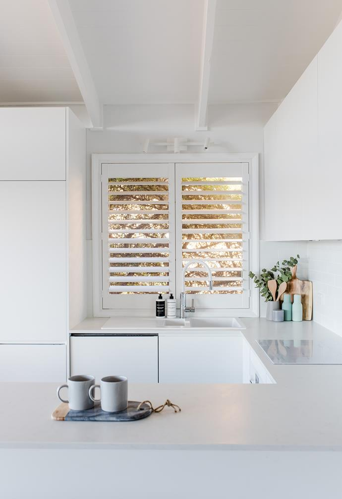**Kitchen** The kitchen continues the white palette in the rest of the apartment. Plantation shutters on the window allow sunlight to enter the space.