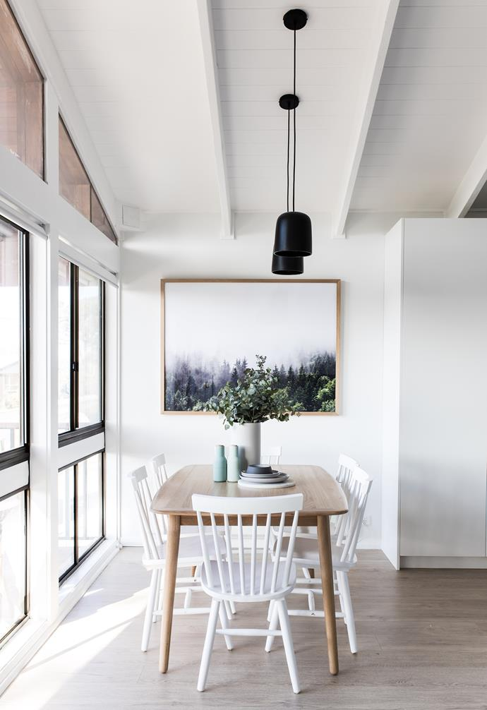 **Dining** A pair of black pendant lamps and large timber dining table are a stark contrast to the white backdrop.