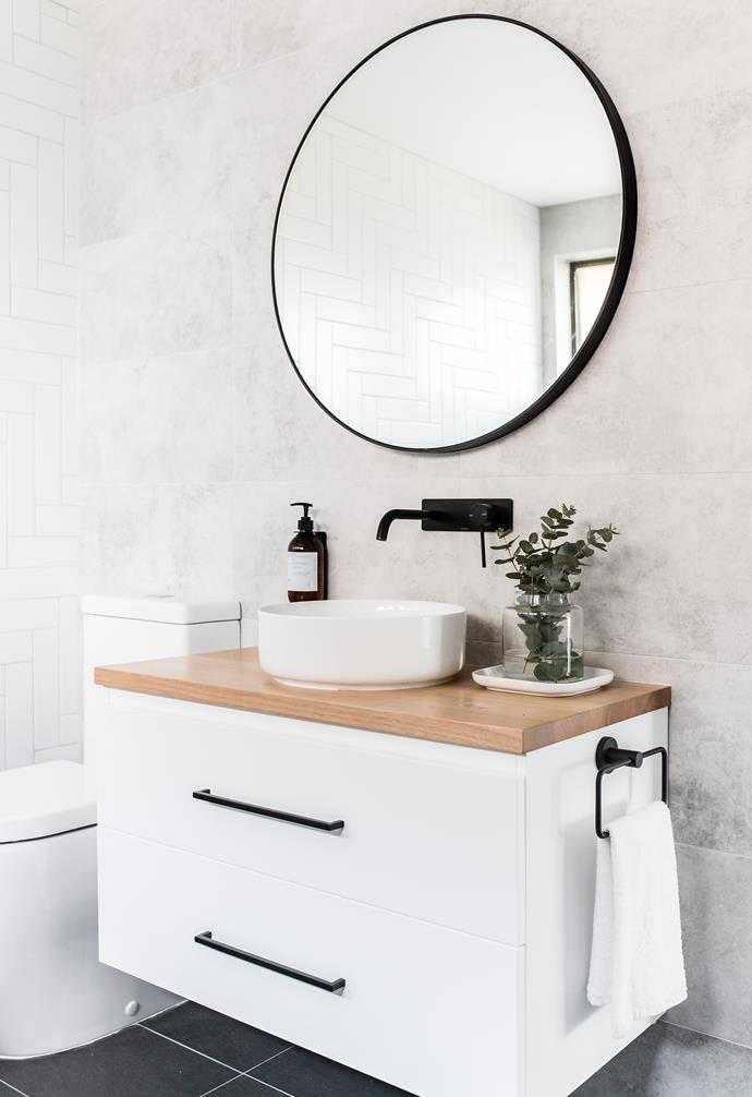 **Bathroom** A circular mirror and clean vanity add a refined touch to the bathroom.