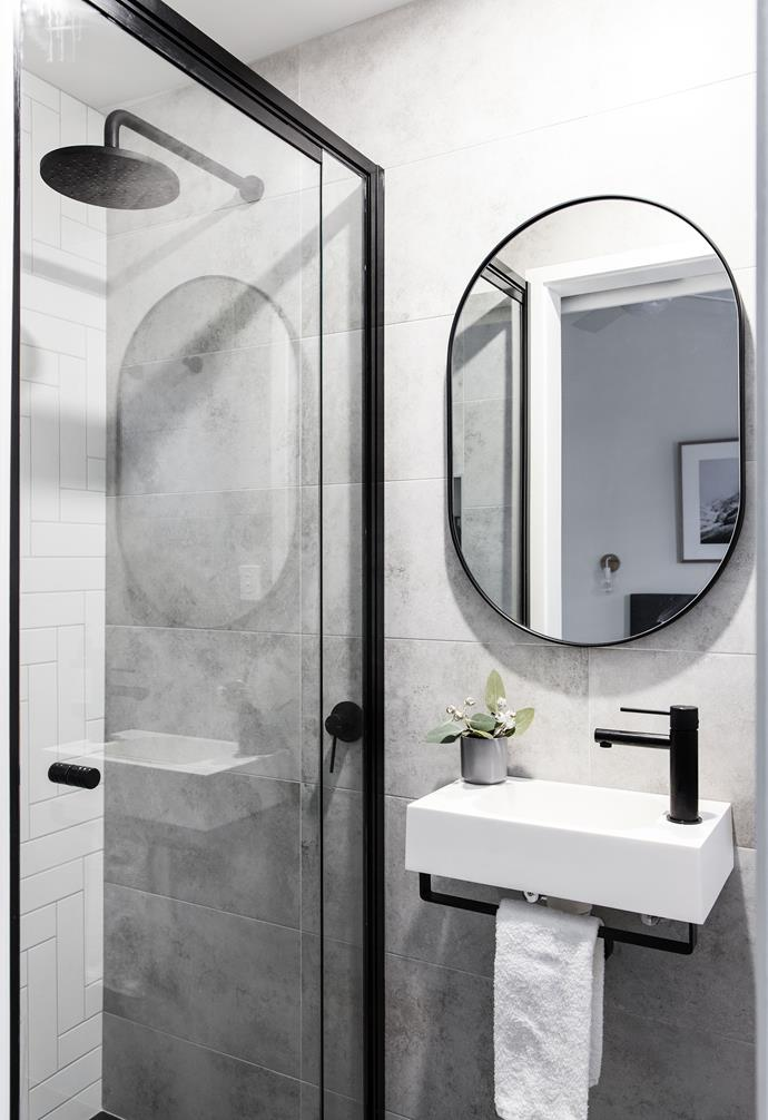 **Bathroom** This bathroom sports a slightly moodier tone with gray tiles and black detailing.
