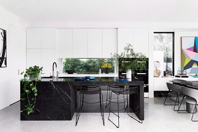 Opening the kitchen to the dining room allows for entertaining and adds lightness. Stealing the show and adding an instant luxe touch to the space with minimum impact, the marbled kitchen island contrasts the white timber joinery, and helps to zone the areas of the communal living space. *Photography: Martina Gemmola / Bauersyndication.com.au*