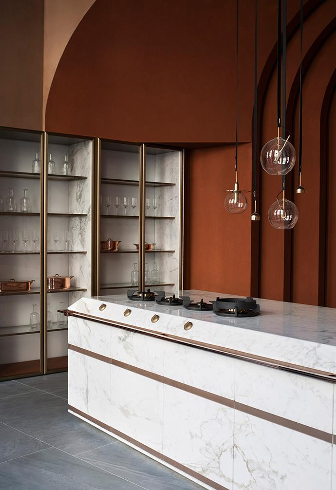"**Ginger** The team say that the marble is ""perfectly connected with the carved design of the kitchen island, characteristic strengthened by the tilted design of the countertop, skirting and the door without handle."" *Photography: courtesy of Fendi Cucine*."
