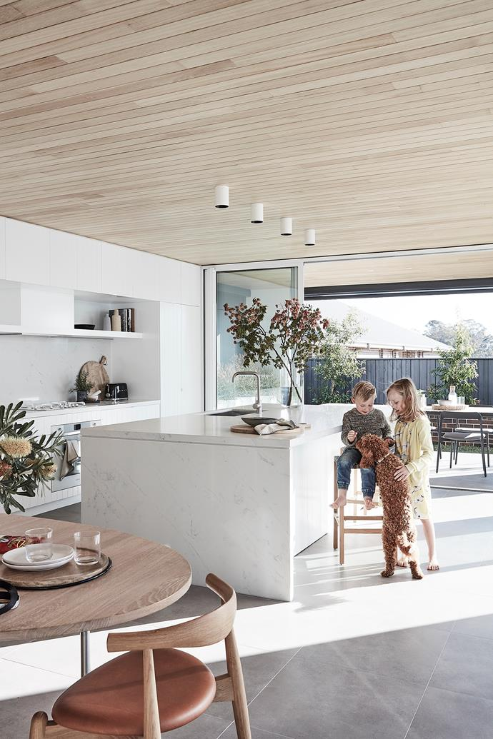 Henry and Thea in the integrated kitchen by Top Knot Carpentry & Joinery. The island and splashback are in Smartstone 'Carrara', while 'Absolut Blanc' features on the rear bench. Oven, cooktop, rangehood, combi oven, dishwasher and coffee machine, all Smeg.