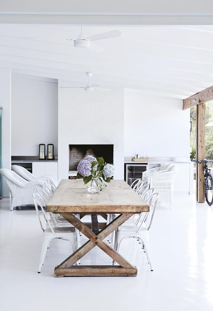 **Outdoor dining area** The family usually eats every meal out here, with ceiling fans keeping the space cool in summer and a roaring fire providing warmth in winter. The custom cedar table was made in Cape Town. *Styling: Sven Alberding | Photography: Warren Heath*.