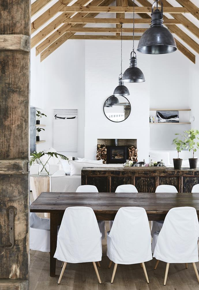 **Open-plan dining and living area** A series of industrial-style pendant lights complement the exposed beams. *Styling: Sven Alberding | Photography: Warren Heath*.
