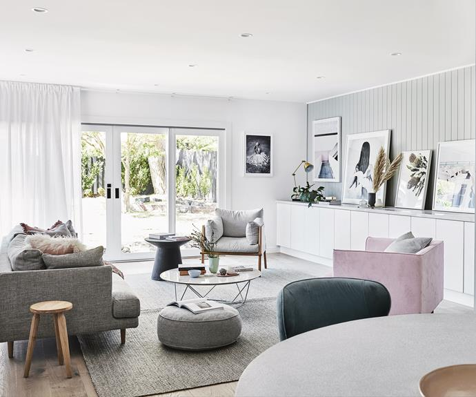 """**Living room** Part of a 1990s extension, this area had lower ceilings than the original parts of the house. """"I used Easycraft 'EasyVJ' panelling painted in Dulux Tranquil Retreat to give the illusion of more height,"""" says homeowner Nat Wheeler. All the furniture, including the GlobeWest sofa, chairs and coffee table and Armadillo&Co rug, is from [Norsu Interiors](https://norsu.com.au/ target=""""_blank"""" rel=""""nofollow""""). Artworks (from left): *Love Warriors - Her* print by Roy Rossovich, *Walkway* print by Middle of Nowhere, *Love warriors - Sky Circles* by Hannah Lemholt & Sara N Bergman, *Matilda 2* print by Donna Delaney, all from [Norsu Interiors](https://norsu.com.au/ target=""""_blank"""" rel=""""nofollow""""). *Ferry trip* by [Middle of Nowhere](http://www.middleofnowhere.com.au/ target=""""_blank"""" rel=""""nofollow"""")."""