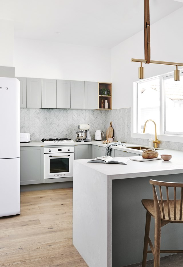 Despite its predominately grey palette, this Scandinavian-inspired kitchen feels warm and inviting thanks to ample natural light, timber furniture and brass fixtures.