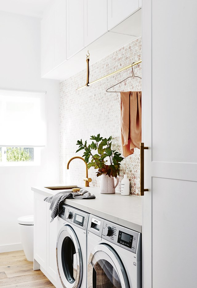 """Side-by-side appliances allow for maximum benchspace with pink marble penny round tiles, gold tapware and a custom-made gold hanging rack up the luxe factor in the laundry of this [Scandinavian inspired family home](https://www.homestolove.com.au/scandi-style-family-home-7108