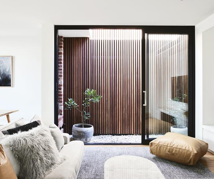 "**Living area** Timber battens in the courtyard provide a warm contrast to the simple neutral palette of the home. Artwork: *Shadow* photographic print by [Maegan Brown](https://maegankb.com/|target=""_blank""