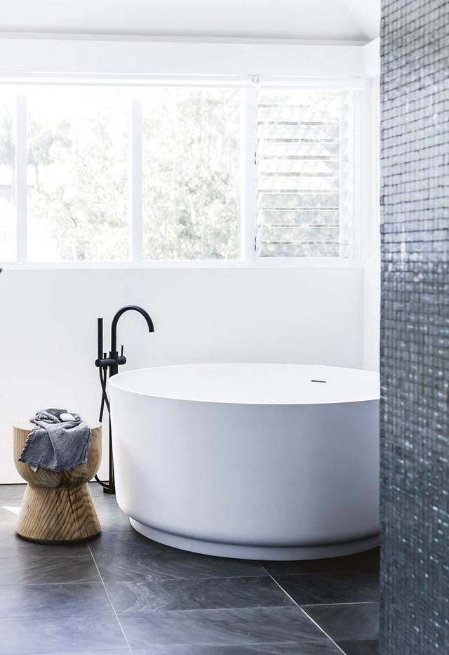 "In this [modern beach house](https://www.homestolove.com.au/modern-beach-house-7133|target=""_blank""), a luxurious round tub takes centre stage in the white bathroom. A glittering wall of mosaic tiles sets the scene for the understated, yet elegant room. *Photo: Maree Homer / Styling: Sarah Ellison*"