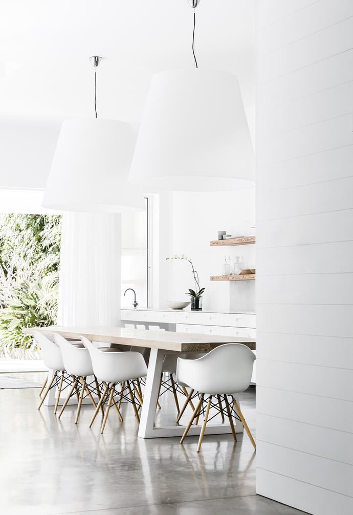**Dining area** Glazed stacker doors open up this space to the garden and pool. White walls throughout in Dulux Lexicon Quarter create a clean, calming mood. Classic Eames 'DAW' dining chairs provide soft curves.