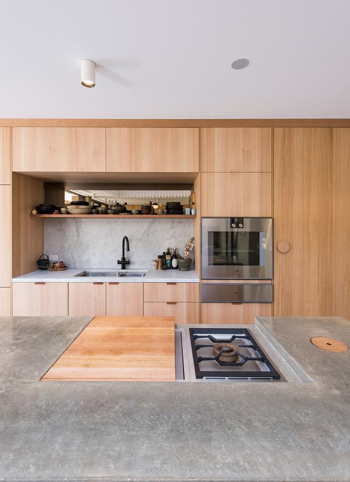 In the kitchen, custom chopping boards can be slid over to conceal the 3-burner cooktop; a simple design that transforms the island from cooking space to entertaining area. The circular timber element cleverly masks a bin chute under the island. *| Photography: David Sievers*