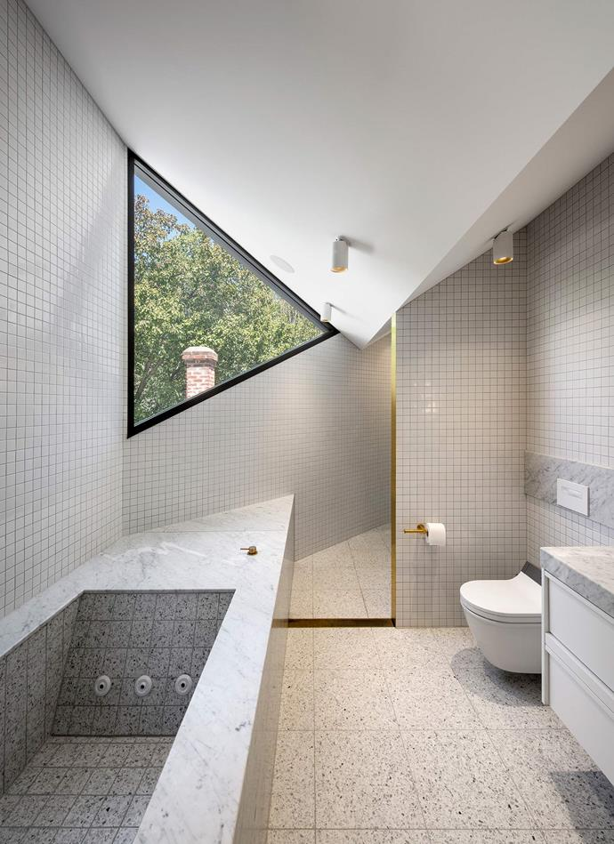 """The bathroom window reflects the cat-eared design, which intercepts the pre-existing fabric of the house. """"There's a marble bathtub, and behind that, you've got the world's biggest shower,"""" says Dave. *