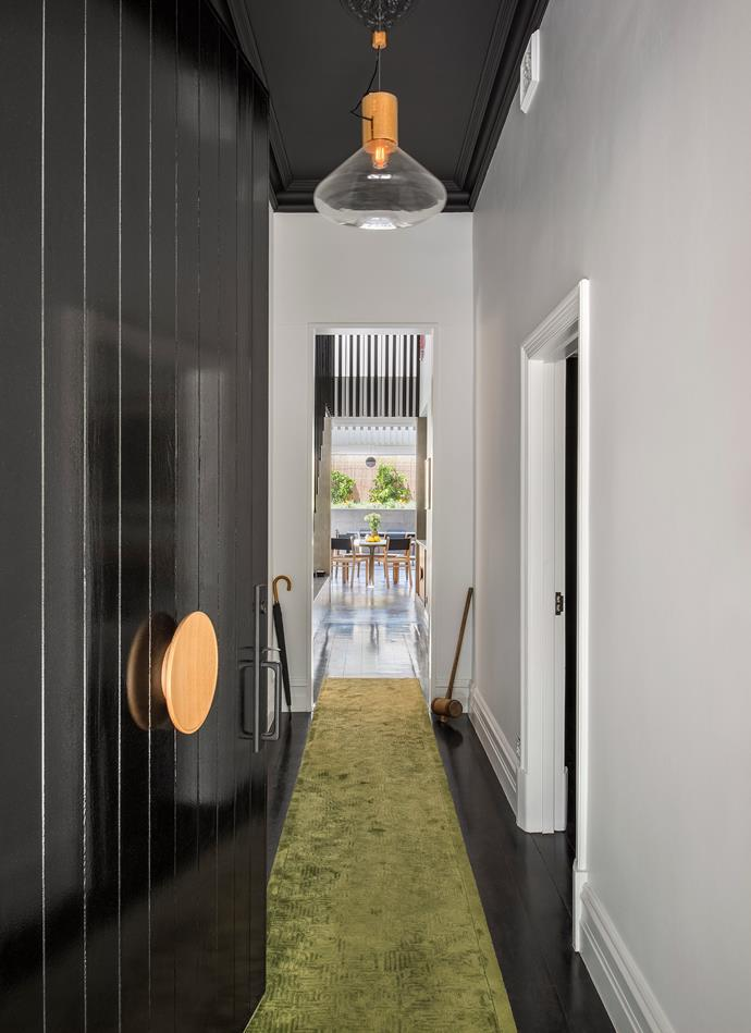 Like a classic symmetrical cottage, the front door opens up to views through the compact home and out to the backyard. A green hallway carpet leads guests towards the open-plan living space. *| Photography: David Sievers*