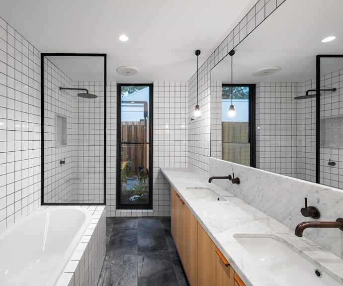 The main bathroom suite in the original cottage features square subway tiles. Timber cabinets beneath the vanity hint at the home's signature timber-clad scheme. *| Photography: David Sievers*