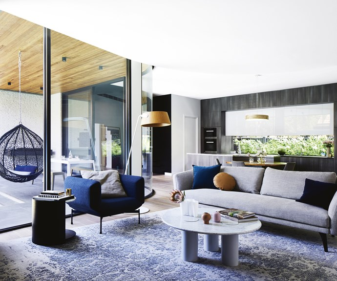 "**Living area** A dramatic curved glass wall floods this open-plan space with sunlight. Homeowner Josie chose a 'Boulevard' sofa from King Living to complement the 'Segment' chair from Meizai and expansive Bayliss rug. Polytec timber veneer cabinetry in Char Oak in the kitchen ensures the palette is refined and elegant. 'Ivy' coffee table, [Grazia & Co](https://graziaandco.com.au/|target=""_blank""