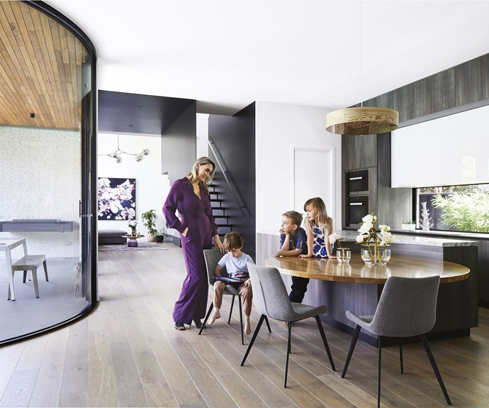 """**Kitchen** Josie with Flynn, Cooper and Abbey in the hub of the home, where the enormous curved glass wall softens the look of the ultramodern extension. 'Cleo' dining chairs, [GlobeWest](https://www.globewest.com.au/