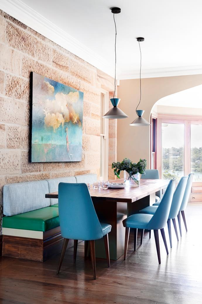 """Melissa wanted a low-maintenance table that could accommodate drop-in guests, says designer Brett Mickan. ""And the full-length banquette fits a pile of children."" The banquette and vintage Paul Kafka chairs are upholstered in family-friendly vinyl. Pendant lights, HG Furniture. Artwork by Melissa Egan."