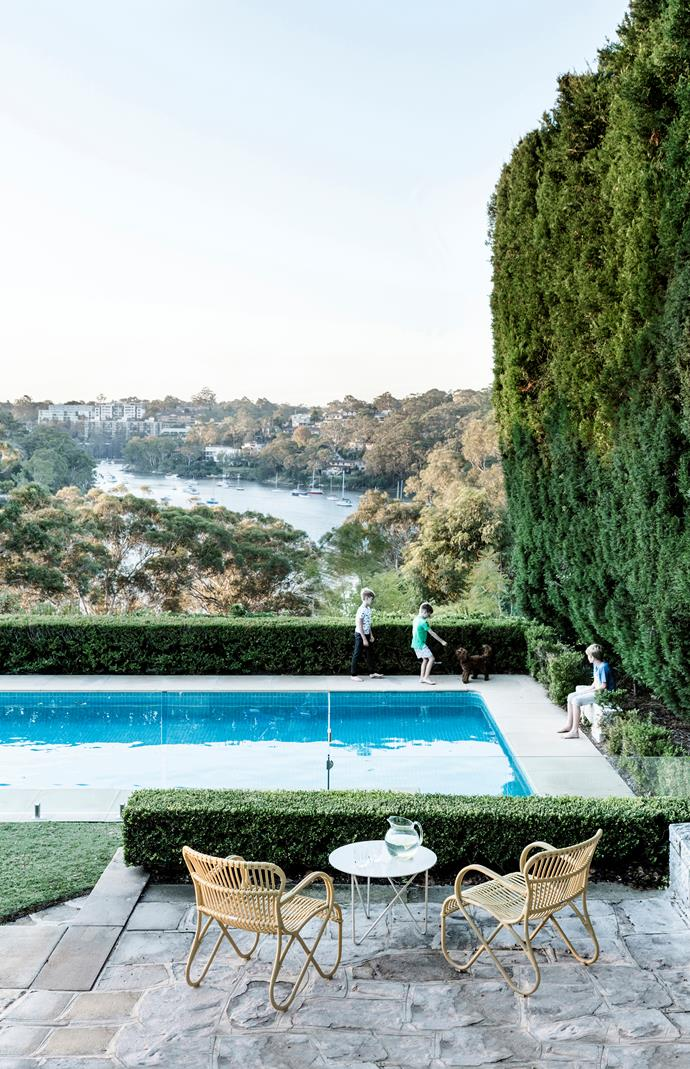 Miller, Will and Harrison play around the pool with cavoodle Luna; behind them is a tree-fringed view of Lane Cove River. 'Fred' table, Jardan. Outdoor chairs, Town & Country Style.